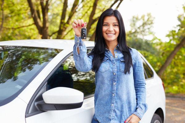 Happy woman with car keys standing by her car