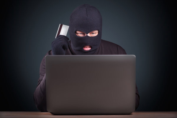 Hacker holding a credit card on wooden background