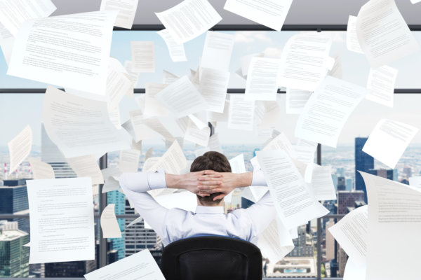 young businessman sitting in office and falling papers