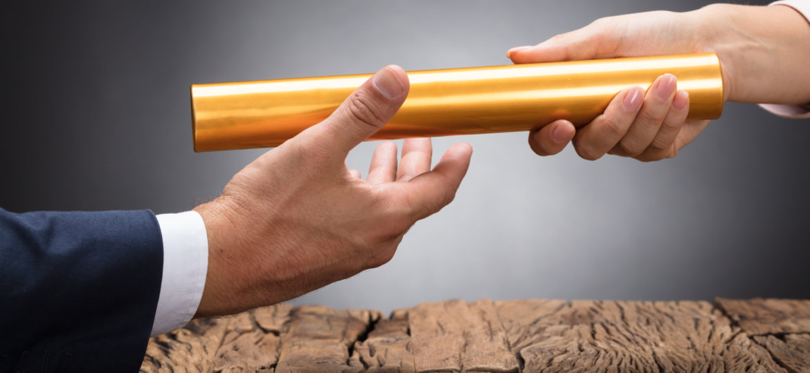 Close-up Of A Businessperson Passing Baton